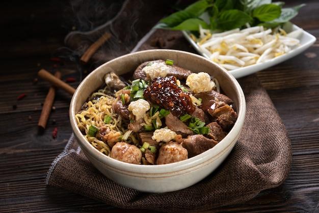 Makaron z wieprzowiną i kulkami wieprzowymi, pasta chilli z zupą po tajsku i warzywami. makaron łódka. selektywne skupienie
