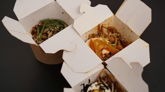 Makaron z wieprzowiną i warzywami w pudełku na wynos na czarnym stole. dostawa azjatyckiego jedzenia. jedzenie w papierowych pojemnikach na czarnym tle