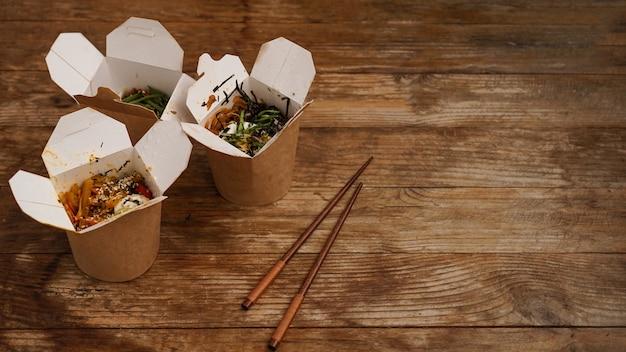 Makaron z wieprzowiną i warzywami w pudełku na wynos na drewnianym stole. dostawa azjatyckiego jedzenia. jedzenie w papierowych pojemnikach na drewnianym tle