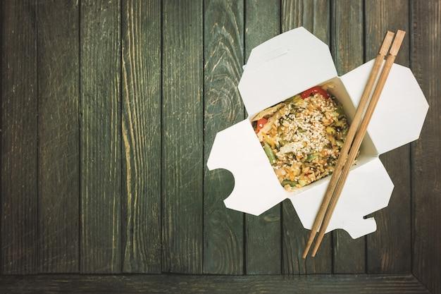 Makaron z woka udon i ryż z owocami morza i kurczakiem w pudełku na czarno