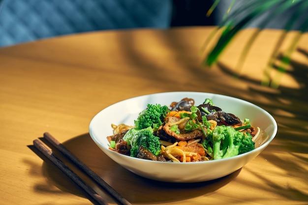 Makaron z woka z wołowiną, warzywami, sosem słodko-kwaśnym i pieprzem syczuańskim. tło drewna. chiński kuzyn