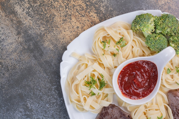 Makaron z zieleniną i koncentratem pomidorowym, mięso na białym talerzu