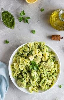 Makaron z zielonym sosem i pieczonym kalafiorem na białym talerzu. skopiuj miejsce