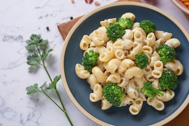 Makaron z zielonymi warzywami i kremowym sosem na białym talerzu. miejsce na kopię widok z góry. leżał płasko.