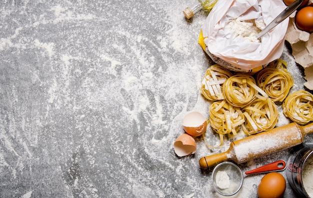 Makaron ze składnikami - mąka, jajka i różne narzędzia do gotowania. na kamiennym stole. wolne miejsce na tekst. widok z góry