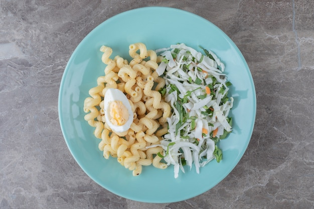Makaron ze świeżą sałatką i jajkiem na niebieskim talerzu.