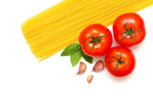 Makaron ze świeżymi pomidorami, bazylią i czosnkiem na białym tle