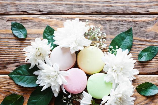 Makaronik z kwiatami na drewnianym stole. urocza kompozycja z francuskiej piekarni z białym kwiatem asteru i zielonymi liśćmi. romantyczny design