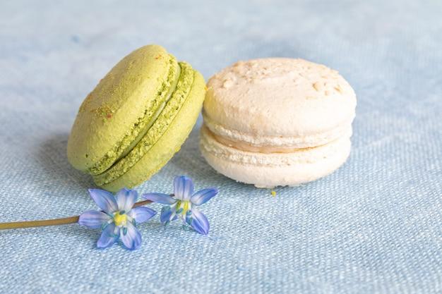 Makaroniki białe i pistacjowe oraz wiosenny kwiat na lnianej serwetce. makaroniki lub makaroniki to francuski lub włoski deser.
