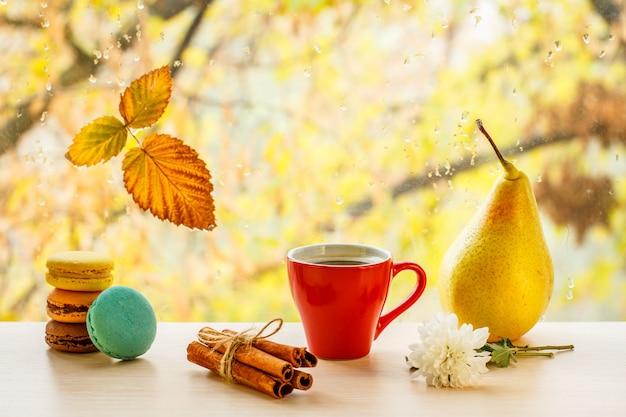Makaroniki, filiżanka kawy, laski cynamonu, gruszka i suchy liść na szybie z kroplami wody w rozmytym tle. opadły liść i krople deszczu na szybie z jesiennymi drzewami w tle.