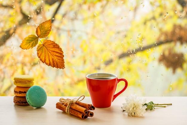 Makaroniki, filiżankę kawy, laski cynamonu i suchy liść na szybie z kroplami wody w rozmytym tle. opadły liść i krople deszczu na szybie z jesiennymi drzewami w tle.