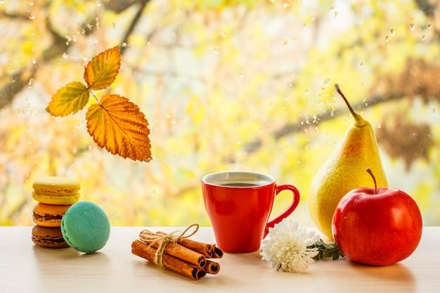 Makaroniki, filiżankę kawy z cynamonem i jesienny żółty liść na szybie z kroplami wody w rozmytym tle.