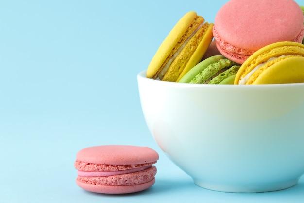 Makaroniki. francuskie ciastka makaroniki wielokolorowe w filiżance. małe francuskie słodkie ciasto na jasnym niebieskim tle. deser. słodycze.