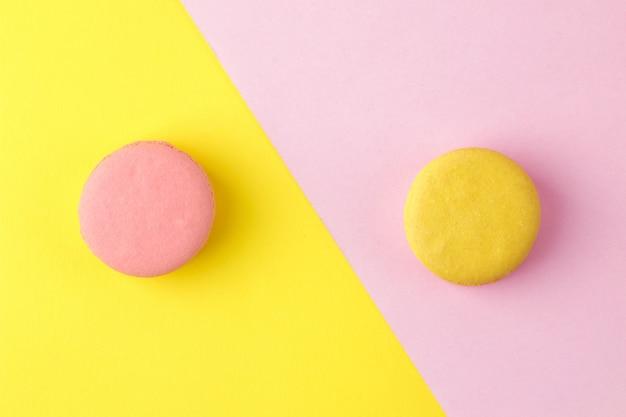 Makaroniki. francuskie wielokolorowe ciasteczka makaroniki. małe francuskie słodkie ciasto na jasnym wielokolorowym różowym i żółtym tle. deser. słodycze. widok z góry
