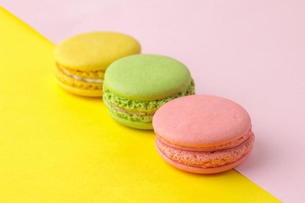 Makaroniki. francuskie wielokolorowe ciasteczka makaroniki. małe francuskie słodkie ciasto na jasnym wielokolorowym różowym i żółtym tle. deser. słodycze.