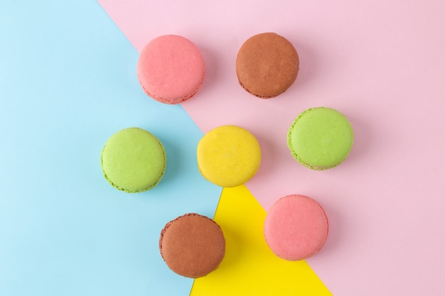 Makaroniki. francuskie wielokolorowe ciasteczka makaroniki. małe francuskie słodkie ciasto na jasnym wielokolorowym tle. deser. słodycze. widok z góry