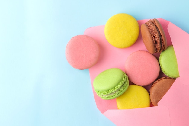 Makaroniki. francuskie wielokolorowe ciasteczka makaroniki w kopercie. małe francuskie słodkie ciasto na jasnym niebieskim tle. deser. słodycze. widok z góry.