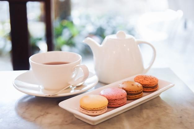 Makaroniki i filiżanka herbaty podawane na stole