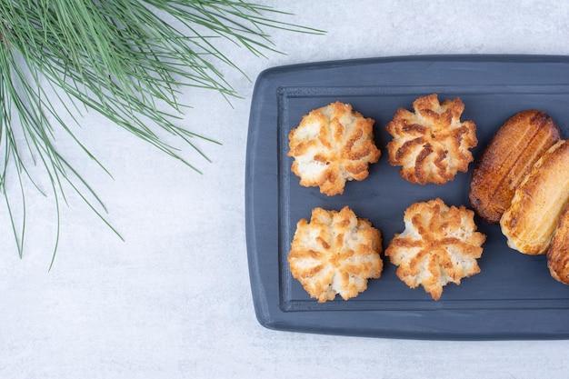 Makaroniki kokosowe i ciastka na ciemnym talerzu z gałęzi sosny. zdjęcie wysokiej jakości