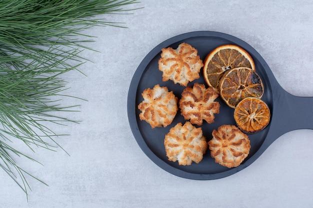 Makaroniki kokosowe na ciemnej desce z plastrami pomarańczy. zdjęcie wysokiej jakości