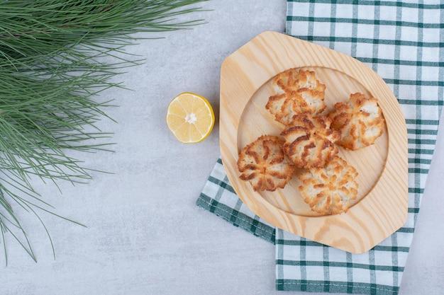 Makaroniki kokosowe na drewnianym talerzu z pół pokrojoną cytryną. zdjęcie wysokiej jakości