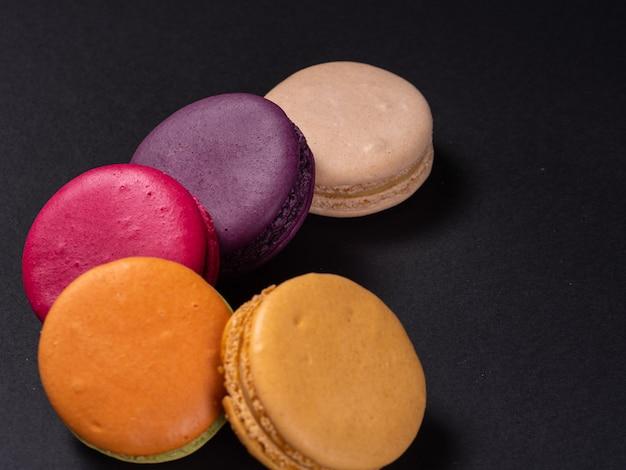 Makaroniki na czarnym stole, słodki i kolorowy deser. gotować w domu.