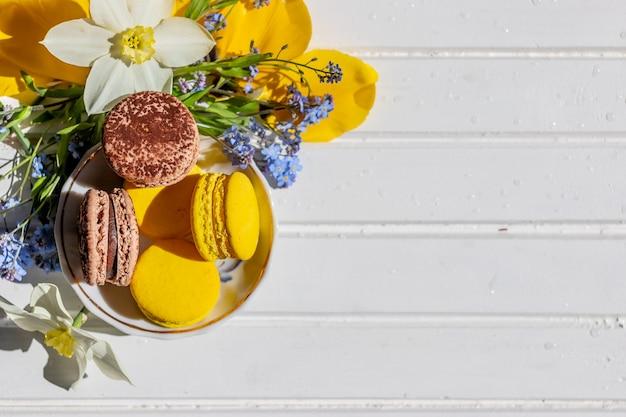 Makaroniki na talerzu na białym drewnianym stole. słodkie macarons i kwiaty. kompozycja z delikatnymi kwiatami kwiatów i francuskim deserem. widok z góry z miejsca kopiowania