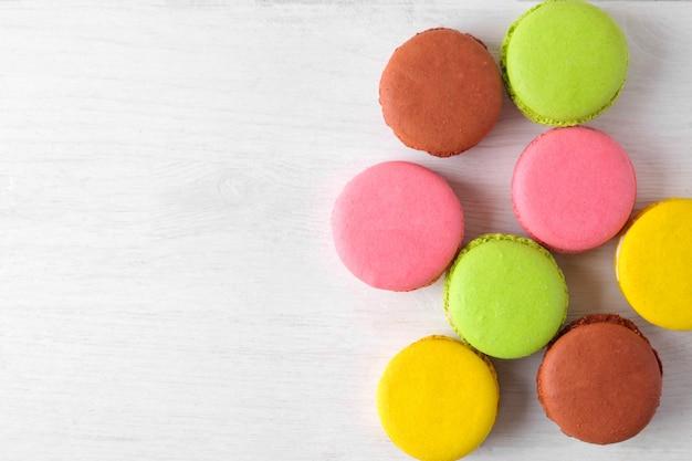 Makaroniki. pyszne kolorowe ciasta francuskie makarony na białym drewnianym stole. miejsce na tekst. widok z góry