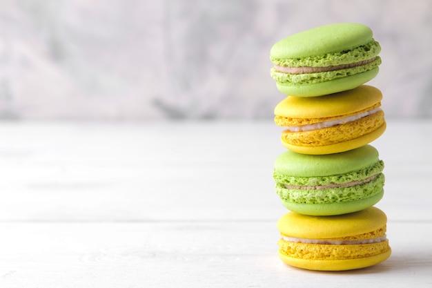 Makaroniki. pyszne kolorowe ciasta francuskie makarony na białym drewnianym stole. miejsce na tekst