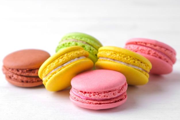 Makaroniki. pyszne kolorowe ciasta francuskie makarony na białym drewnianym stole.