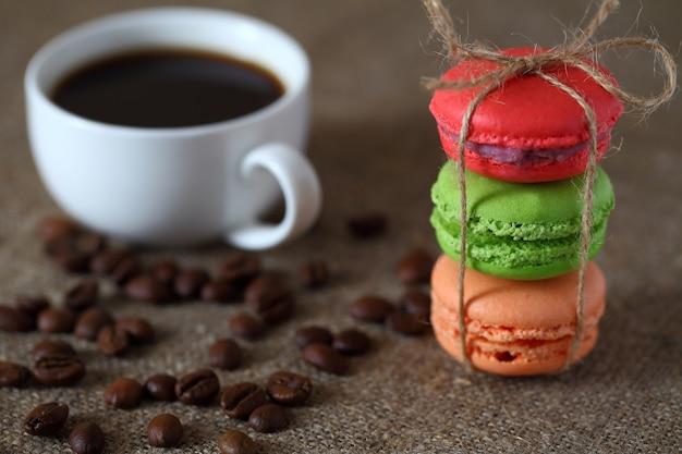 Makaroniki trzy kawałki czerwony, zielony i pomarańczowy związane sznurem i kubek z kawą, ziarna rozproszone na płótnie obrus.