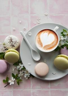 Makaroniki z filiżanką kawy i gałązką białych kwiatów na różowej powierzchni płytek