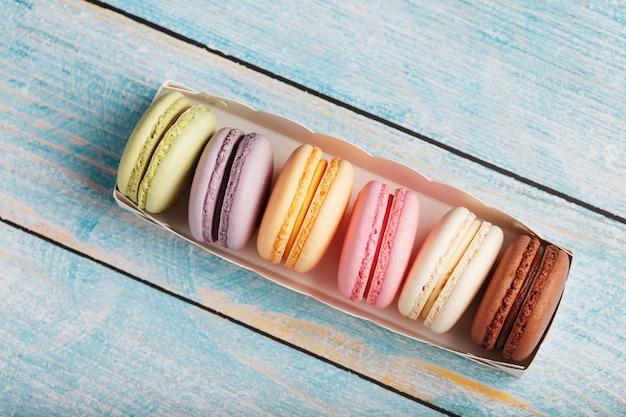 Makaronowe ciasteczka w różnych kolorach w pudełku na niebieskim, starym drewnianym tle niebieskiego koloru.