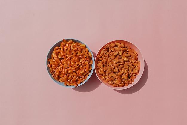 Makaronowe przekąski z bardzo ostrymi przyprawami są w dwóch miseczkach z pastelowym różowym tłem