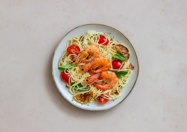 Makaronowe spaghetti z krewetkami, pomidorami, czosnkiem, szpinakiem i cytryną. kuchnia włoska. owoce morza. dieta.