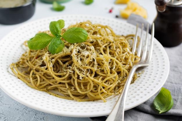 Makaronowe spaghetti z sosem pesto, bazylią i parmezanem na białym talerzu ceramicznym i szarej betonowej powierzchni