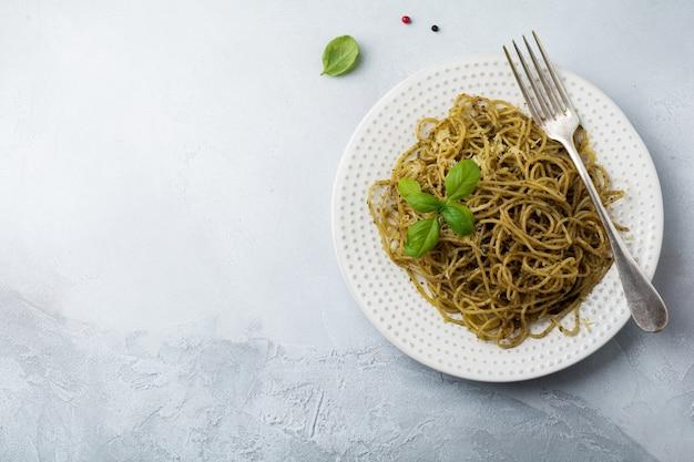 Makaronowe spaghetti z sosem pesto, bazylią i parmezanem na białym talerzu ceramicznym i szarej powierzchni z betonu lub kamienia. tradycyjne włoskie danie. selektywna ostrość.