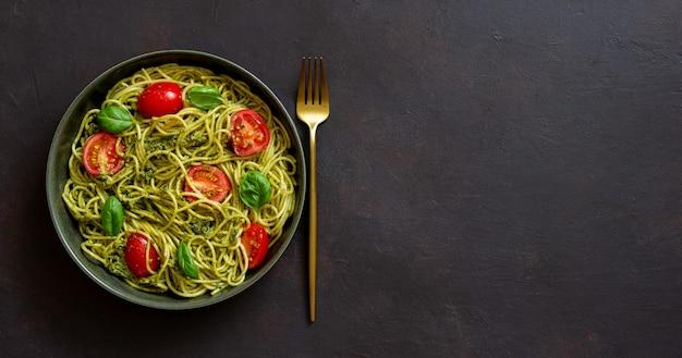 Makaronowe spaghetti z sosem pesto, pomidorami i bazylią. zdrowe odżywianie. jedzenie wegetariańskie.