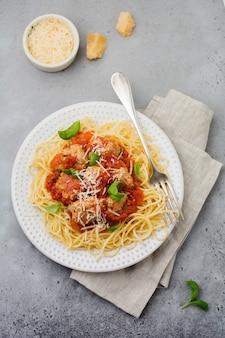 Makaronowe spaghetti z sosem pomidorowym, parmezanem, bazylią i klopsikami na białym talerzu ceramicznym na szarej powierzchni betonowej lub kamiennej. selektywna ostrość.