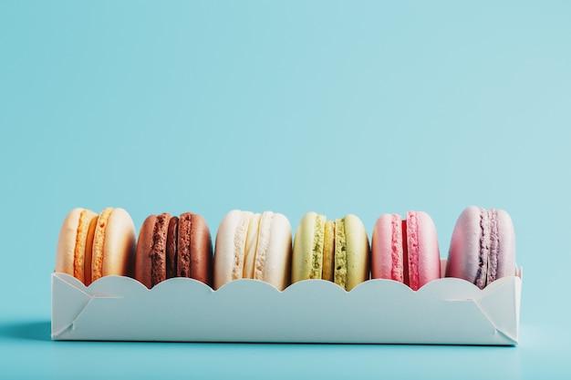 Makaronowi ciastka różni kolory w białym pudełku na błękitnym tle.