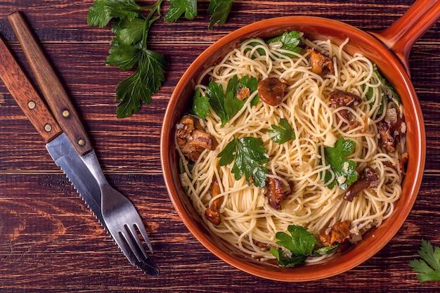 Makaronu spaghetti z kurkami ono rozrasta się na drewnianym tle.
