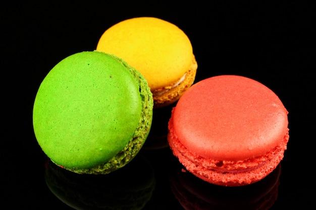 Makarony kolorowe ciasteczka cukiernicze na czarnej powierzchni
