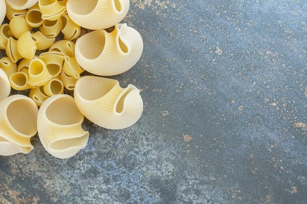 Makarony niegotowane i gotowane w misce, na marmurowej powierzchni.
