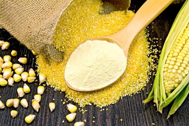 Mąkę kukurydzianą w łyżce, kasze w worze i na stole kolbę na tle drewniane deski