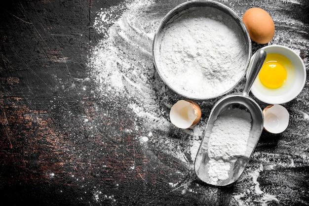 Mąkę na sicie i miarkę z jajkami. na ciemnej rustykalnej powierzchni