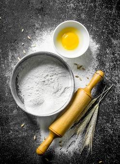 Mąkę na sicie z wałkiem i kłoskami na ciemnym rustykalnym stole