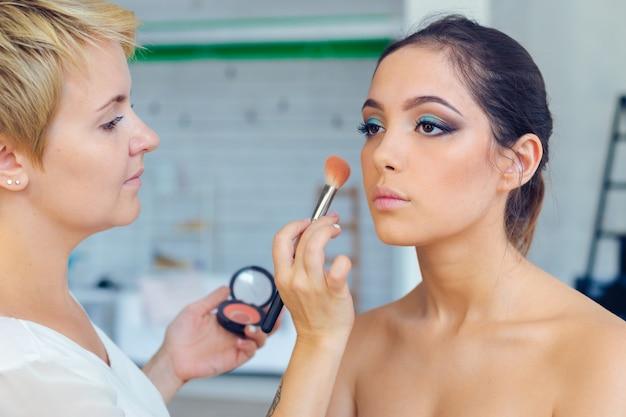 Make up artist robi profesjonalny makijaż młodej kobiety
