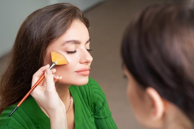 Make up artist stosując profesjonalny makijaż tonalny podkład na twarzy pięknej młodej kobiety rasy kaukaskiej w makijażu pokoju. baza pod makijaż.