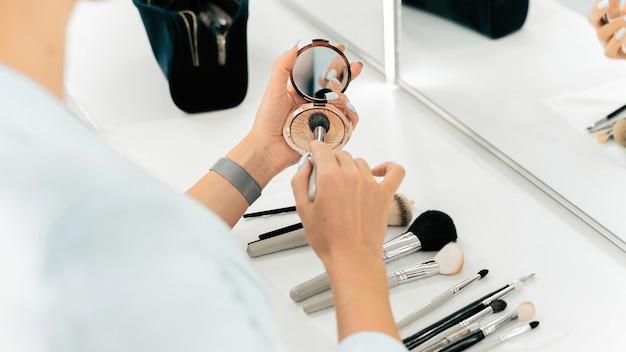 Make-up master nakłada puder za pomocą pędzla