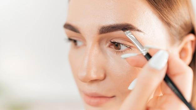 Make-up master robi makijaż dla klienta. malowanie brwi